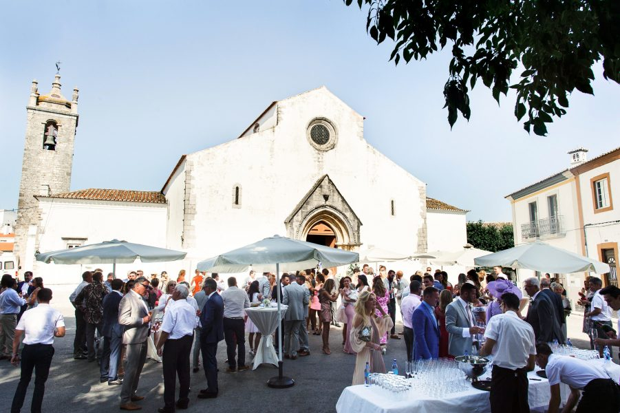 Wedding guests enjoying drinks reception in Portuguese square with church in background Loule Algarve Portugal