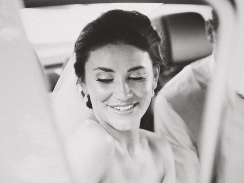 Black and white portrait of Bride's happy face as she steps into wedding car Loule Algarve Portugal