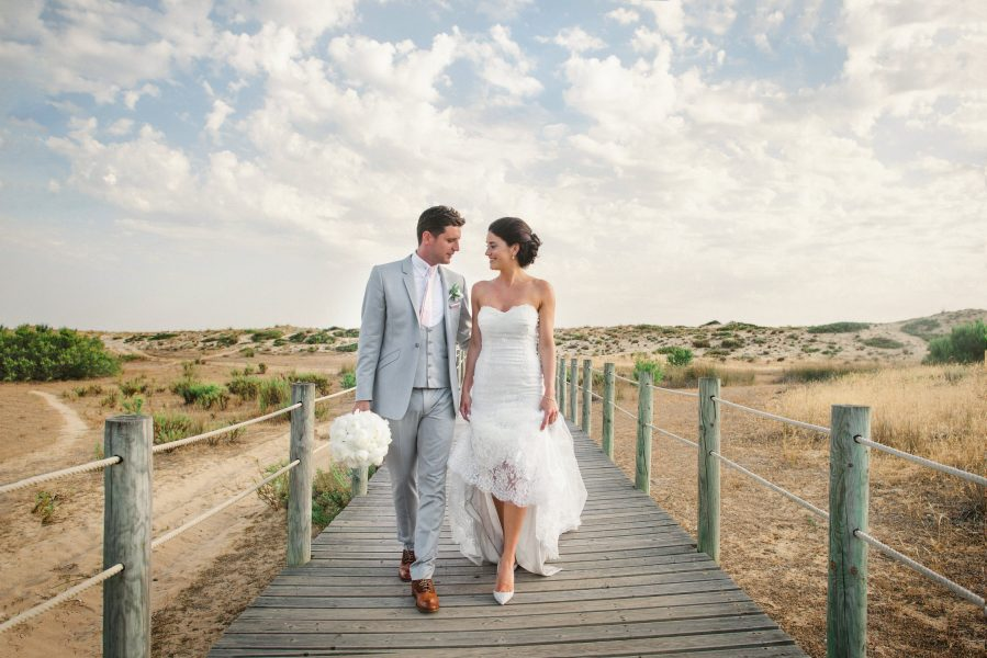 Fine art portrait of Bride and Groom as they down a walkway over beach with sand dunes and dramatic clouds backdrop Quinta Do Lago