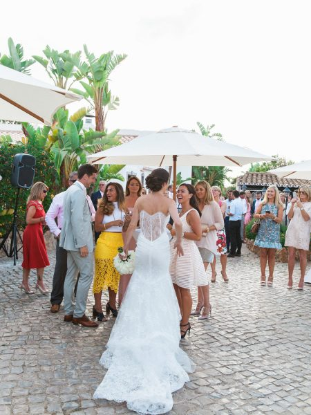Bride showing delicate detail of back of wedding dress chats to guests during drinks reception Quinta Do Lago Algarve Portugal