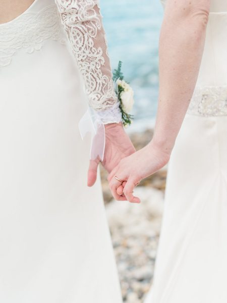 Two brides holding hands on a beach