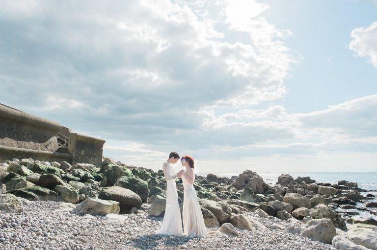 Two brides same sex wedding portrait against dramatic rocks on Chesil beach
