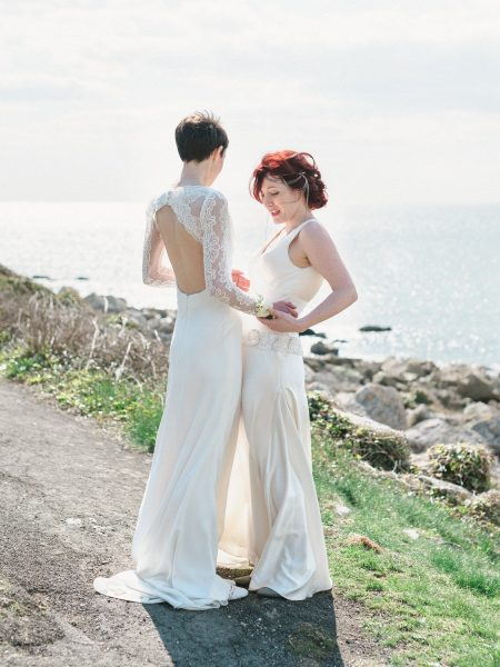 Two brides same sex wedding full length portrait set on a cliff top above Chesil beach