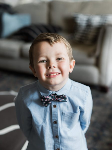 Cute page boy smiling wearing a bow tie and blue shirt in Stone House B and BChesil beach
