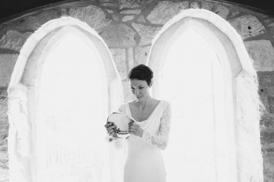 Bride looking in mirror with light streaming in chapel windows at Stone House B and B Chesil beach
