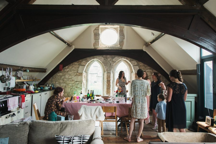 Cnadid of bridal preparations including brides and friends under pitched rood of Stone House converted chapel B and B Chesil beach