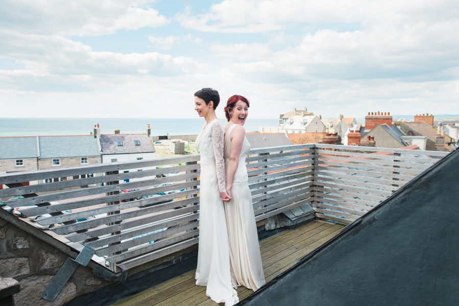 First look of a two bride same sex couple on rooftop Stone House B and B Chesil beach