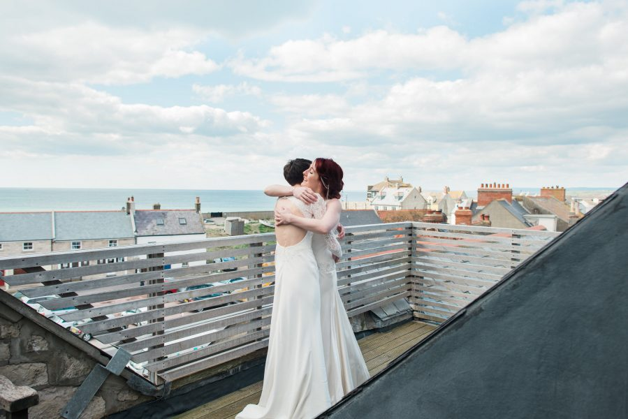 First look of a two bride same sex couple hugging on rooftop Stone House B and B Chesil beach