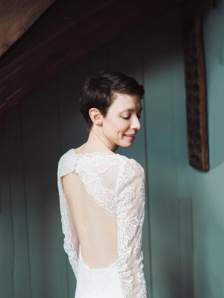 Portrait of bride with short brown hair and beautiful detail of back of wedding dress