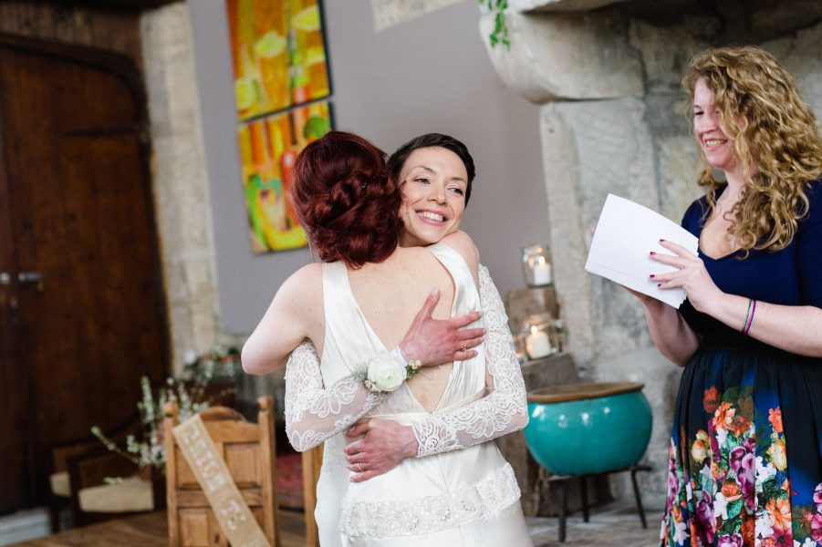 Two brides same sex wedding hug during ceremony in Stone House converted chapel Chesil Beach