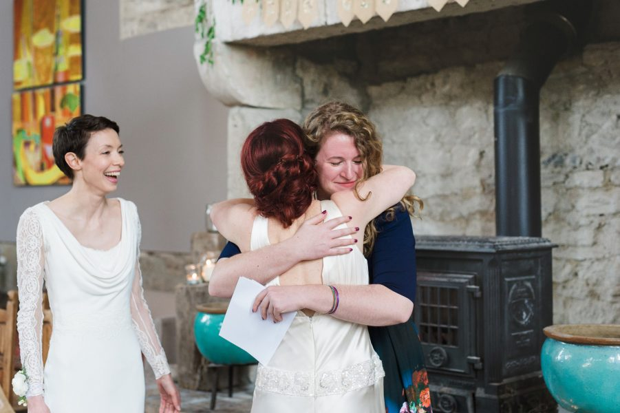 Bride hugs friend post ceremony in Stone House converted chapel Chesil beach