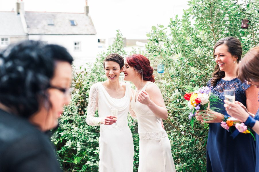 Two brides same sex wedding chat happily post wedding in back yard of Stone House converted chapel Chesil beach