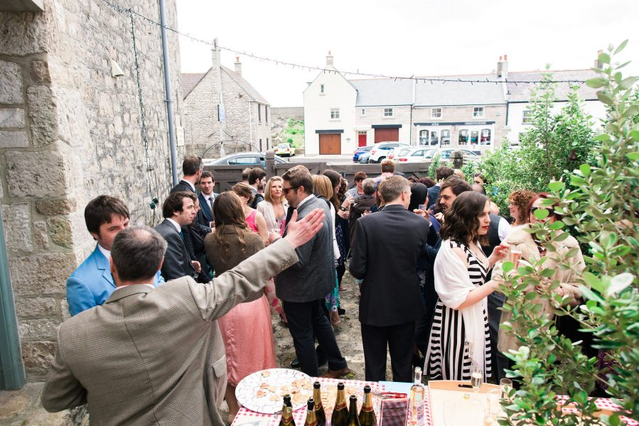 Wedding drinks reception in back yard in Stone House converted chapel Chesil beach