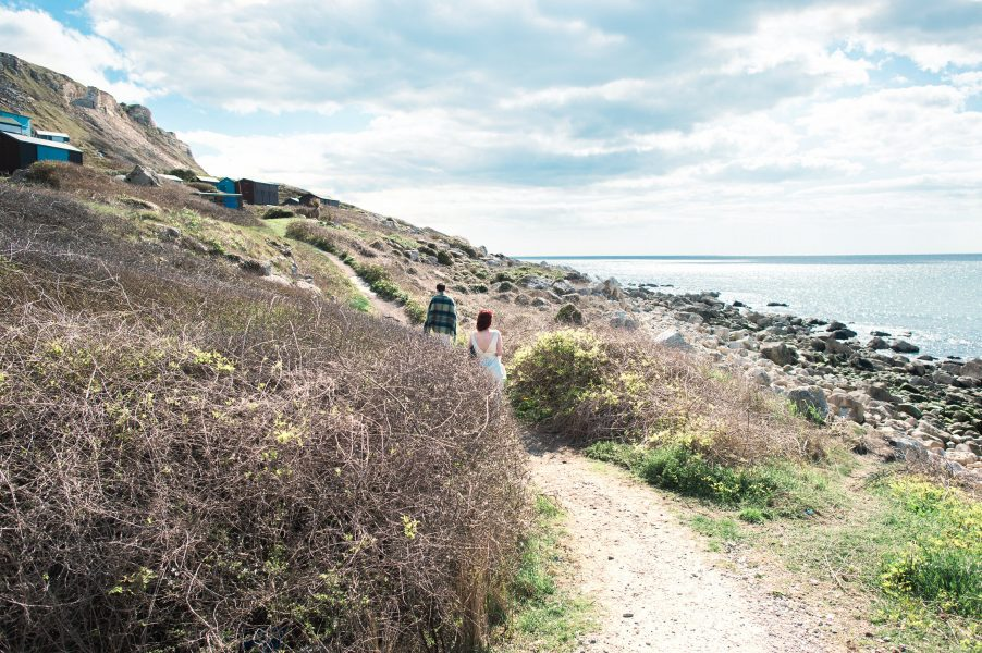 Two brides same sex wedding walk along cliff top heathland path above Chesil Beach
