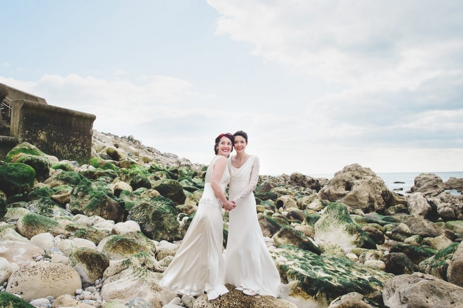 Two brides same sex wedding full length portrait on rocks with green seaweed on Chesil beach