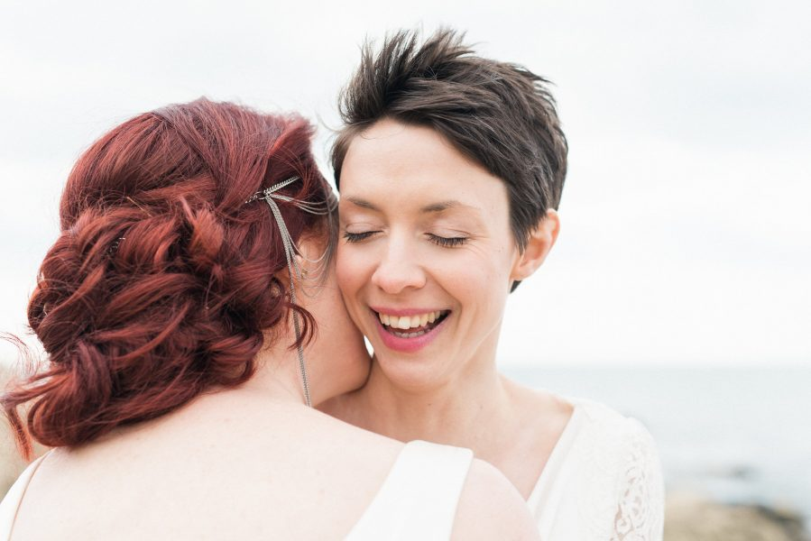 Close up portrait of two brides same sex wedding Chesil Beach Dorset