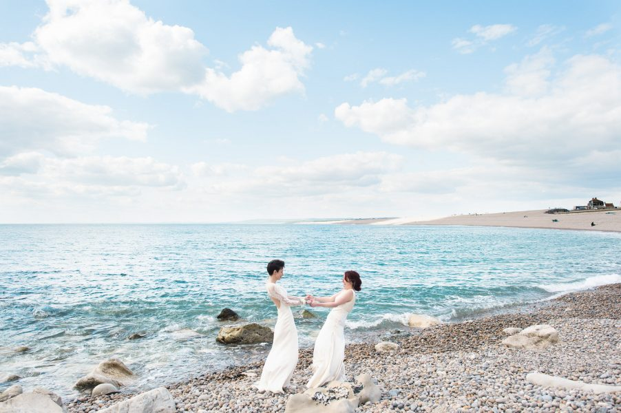 Two brides dance on Chesil Beach as part of their same sex wedding in Dorset
