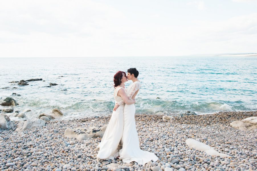 Two brides kissing with beautiful sea backdrop on Chesil beach
