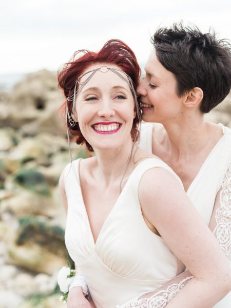 Two brides smiling on Chesil Beach same sex wedding Dorset