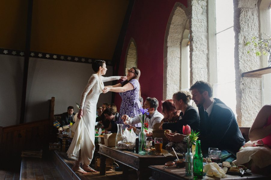 Wedding breakfast scene with barefoot bride hugging guest in converted chapel Stone House Chesil Dorset