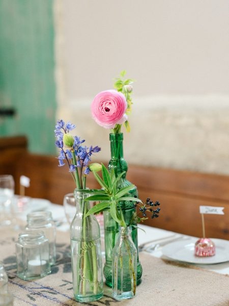 Rustic flowers and coloured bottles decorating wedding table in a converted chapel Stone House Chesil Dorset