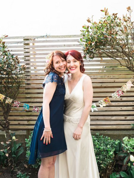 Bride and Maid of Honour portrait in back yard with bunting Stone House CHesil Beach