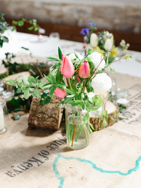 Tulip rustic flowers vintage bottle on coffee sacks table decor Stone House converted chapel Chesil Beach