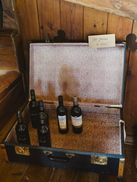 Suitcase with help yourself wine bottles for wedding at Stone House Chesil Beach