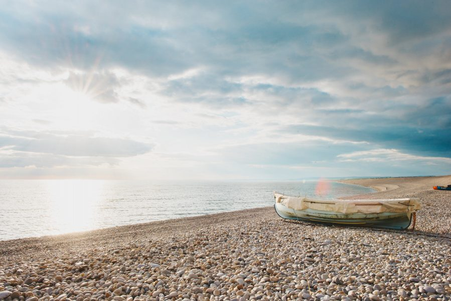 Chesil beach with boat on shore as sun setting Dorset