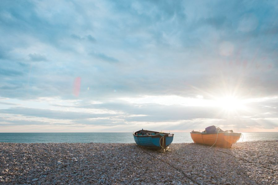 Chesil beach with boats on shore as sun setting Dorset