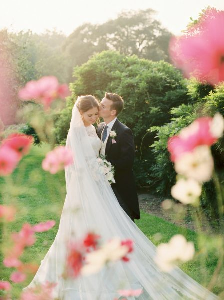 Fine Art wedding couple kissing with pink flowers all around them at Fulham Palace London