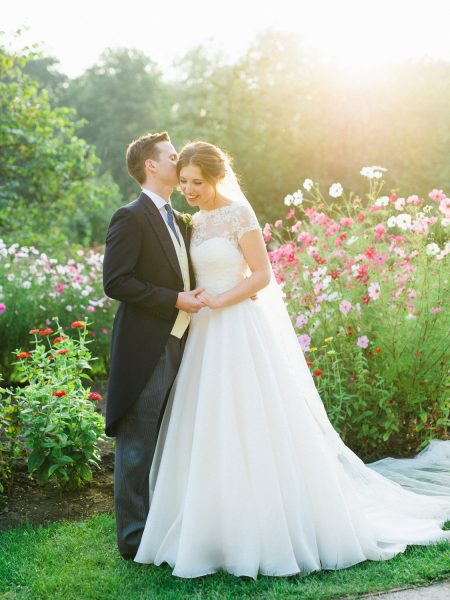 Fine Art wedding couple full length portrait of Groom whispering in Bride's ear with pink flowers in background at Fulham Palace London