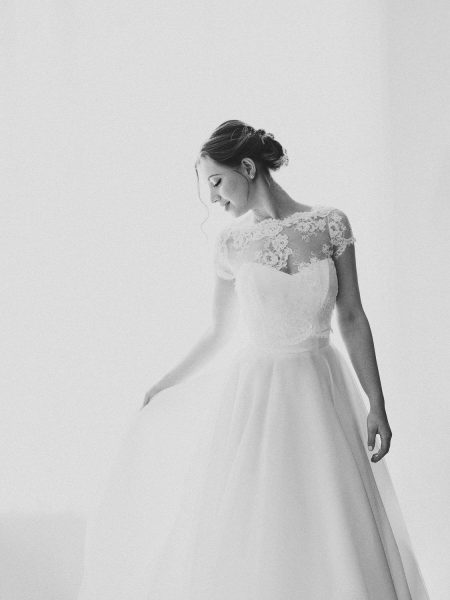 Black and white fine art wedding portrait of bride swishing dress at Rosewood hotel London