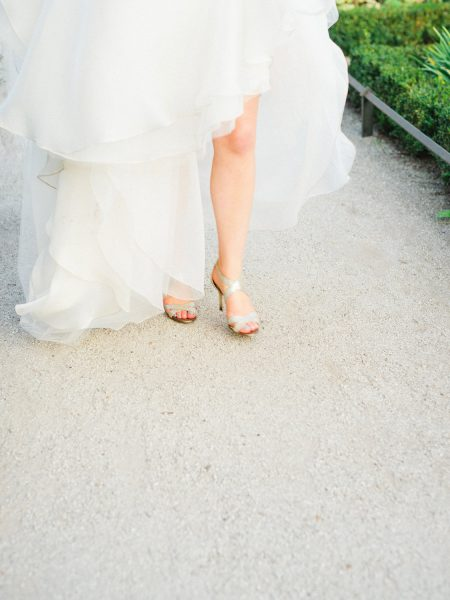 Bride walking with gold metalic Jimmy Choo wedding shoes