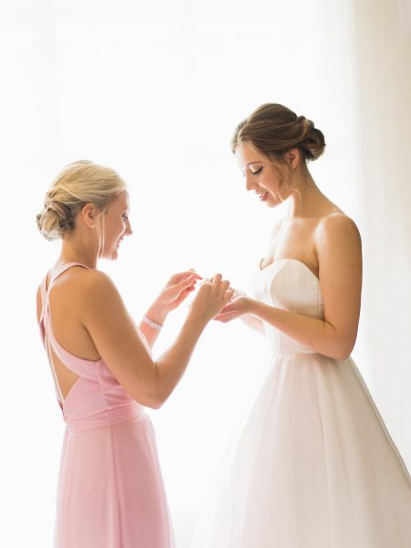Bridesmaid in pink dress helping Bride with earrings at Rosewood hotel London