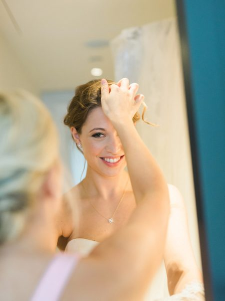 Bride smiling as bridesmaid helps her with her hair during Bridal Preparations at Rosewood hotel London