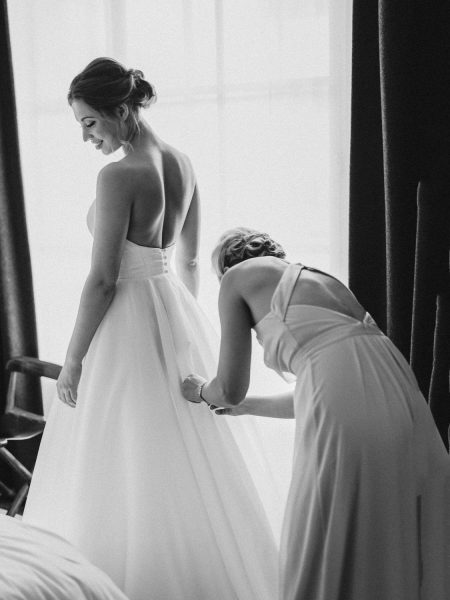 Black and white image of bridesmaid dressing Bride by window at Rosewood hotel London