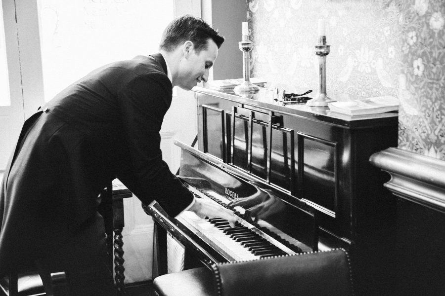 Black and white image of Groom playing the piano pre ceremony