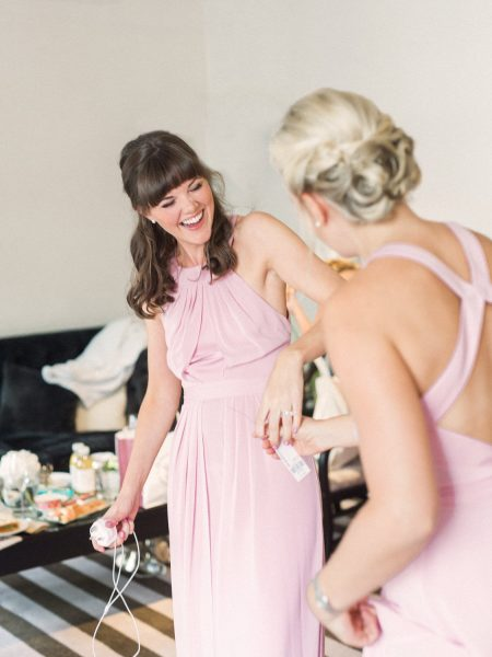 Happy bridesmaids in pink gowns laughing during Bridal Preparations