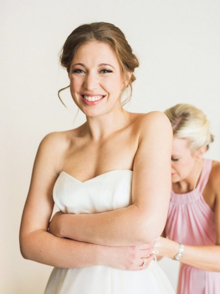 Bride smiling holding her dress up as bridesmaid in pink dress ties up the back at Rosewood hotel London