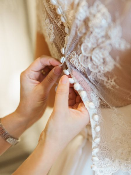 Bridesmaid doing up Bridal lace buttons os back of dress at Rosewood hotel London