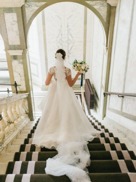 Bride walking down grand hotel staircase at Rosewood London hotel