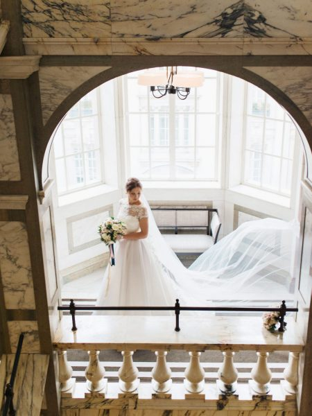Bride walking down grand hotel staircase framed by arch at Rosewood London hotel