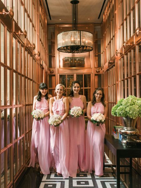 Bridesmaids in pink dresses walking towards camera in mirrored copper hallway at Rosewood hotel London