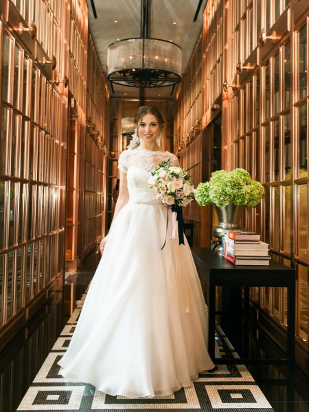 Bride walking towards camera in mirrored copper hallway at Rosewood hotel London