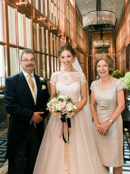 Portrait of Bride with parents standing in mirrored copper hallway at Rosewood hotel London