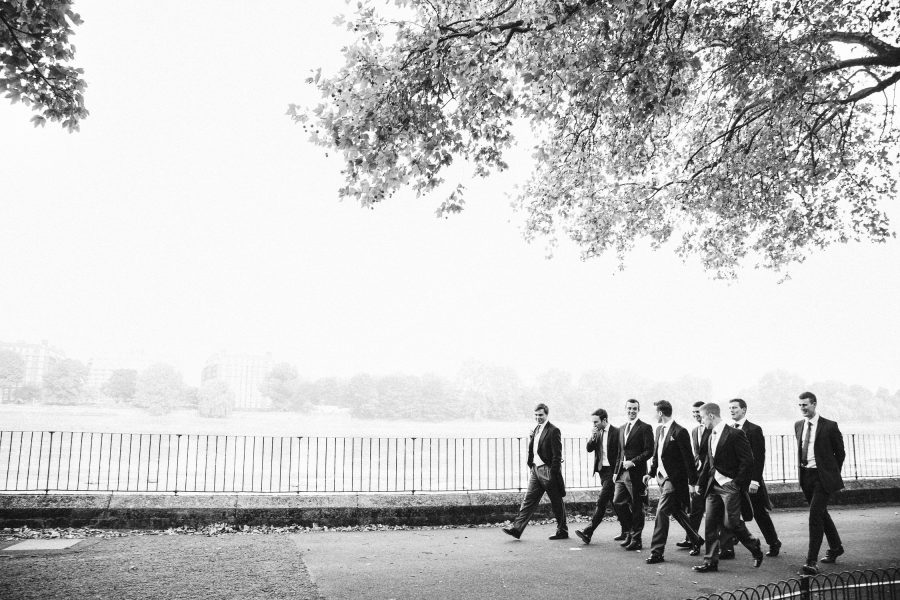 Black and white photo of Groom, Best Man and ushers walking along the river Thames London pre ceremony