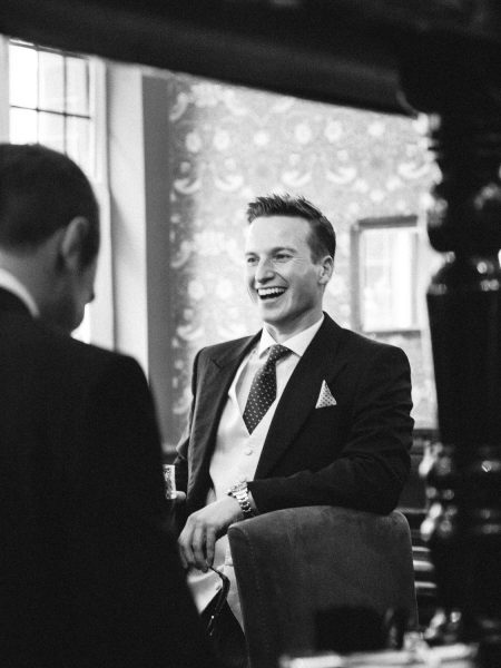 Groom laughing while enjoying pre ceremony drink in London pub