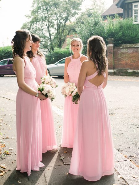 Bridesmaids in pink dresses congregate outside church at Fulham Palcae London