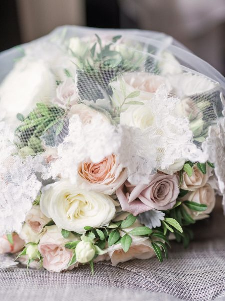 Fine art wedding bouquet in pastel pinks, blush and cream antique roses under delicate veil